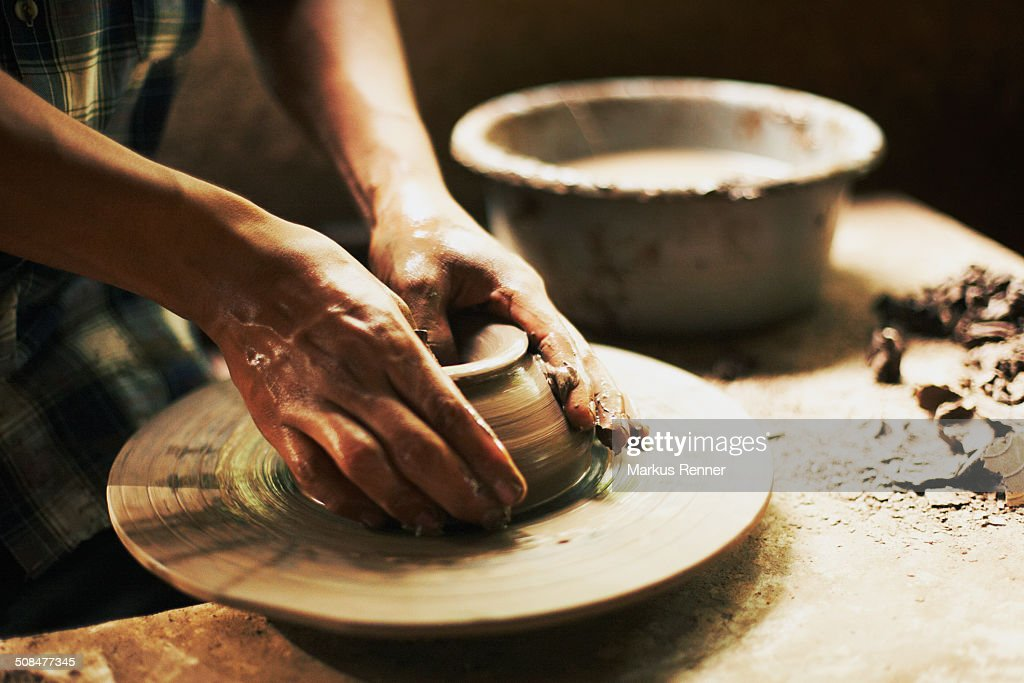 Cropped image of potter moulding clay in workshop : Stock Photo