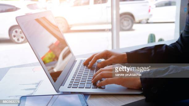 Cropped image of professional businesswoman working at her office via laptop, young female manager using portable computer device while sitting at modern loft, flare light, work process concept
