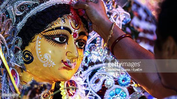 cropped image of pundit applying sindoor to durga statue during durga puja festival - west bengal stock pictures, royalty-free photos & images