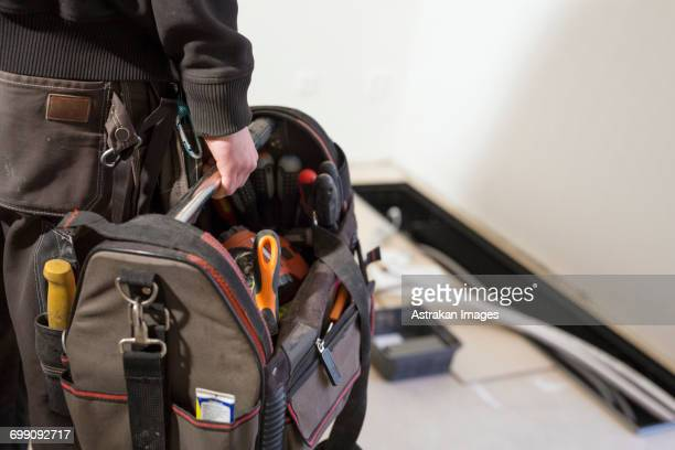 Cropped image of repairman carrying toolbox