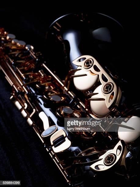 Cropped image of saxophone against black background