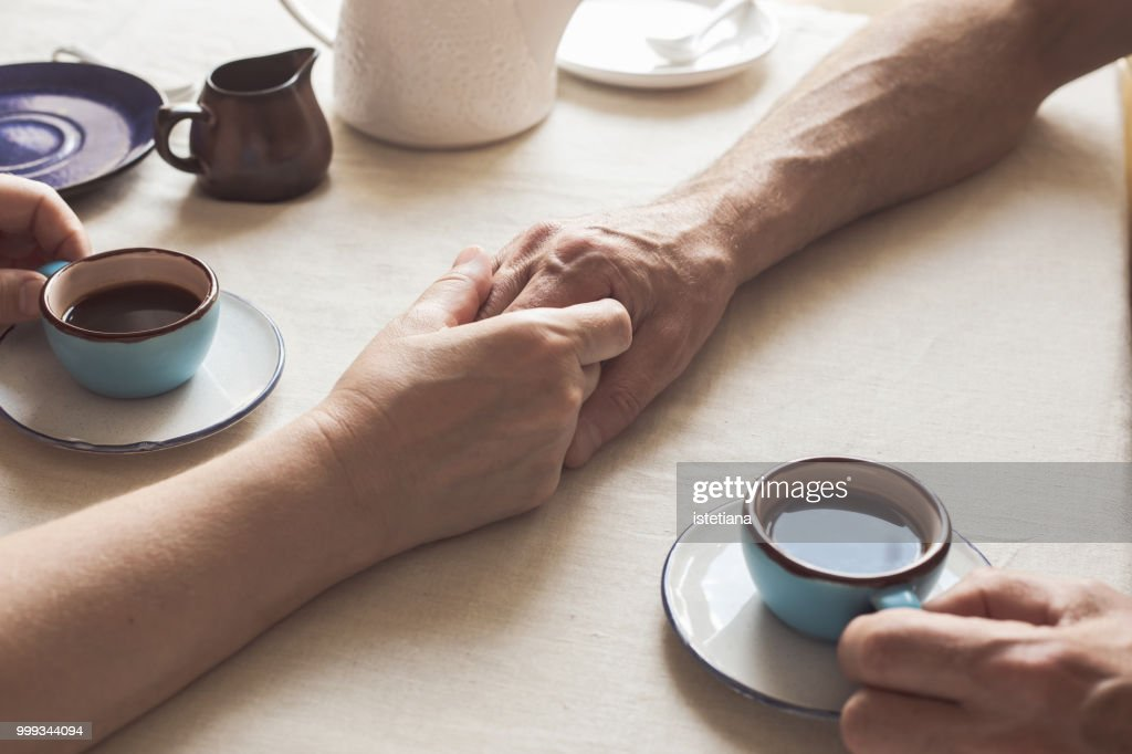 Cropped image of senior couple holding hands and drinking coffee : Stock Photo