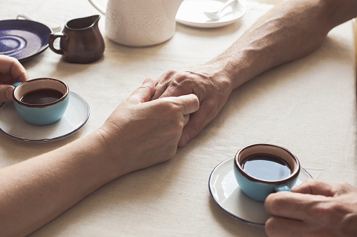 Cropped image of senior couple holding hands and drinking coffee - gettyimageskorea