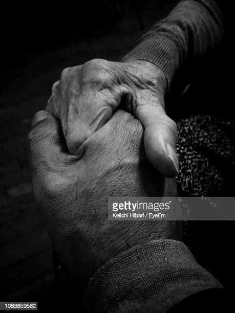 cropped image of senior couple holding hands - black and white hands stock pictures, royalty-free photos & images