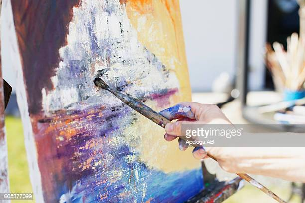 cropped image of senior female artist painting canvas outdoors - easel stock pictures, royalty-free photos & images