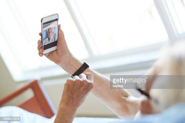 Cropped image of senior man taking selfie with smart phone in hospital ward