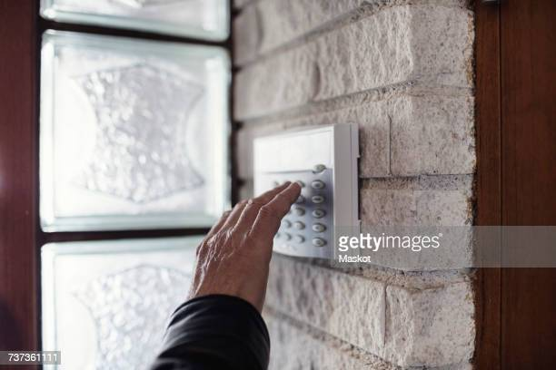 Cropped image of senior man using electronic lock on wall outside house