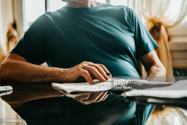 cropped image of senior men writing crossword on newspaper - human body part stock pictures, royalty-free photos & images
