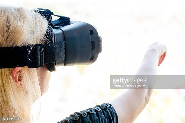 Cropped Image Of Senior Woman Gesturing While Using Virtual Reality Simulator