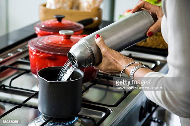 Cropped Image Of Senior Woman Pouring Water In Container On Stove