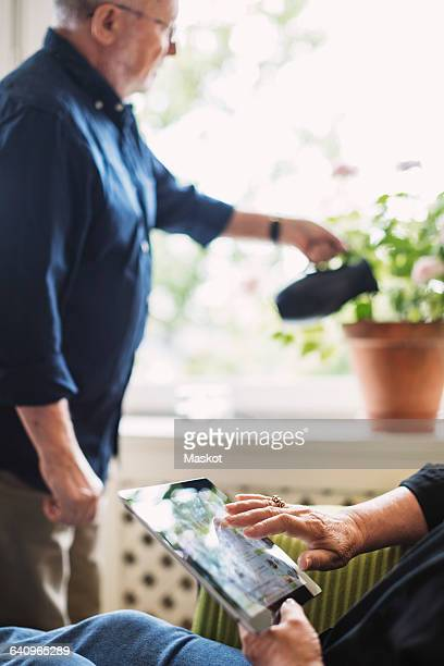 Cropped image of senior woman using digital tablet while man watering flower plant