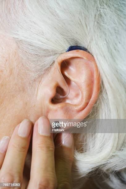 cropped image of senior woman wearing hearing aid - ear canal stock-fotos und bilder