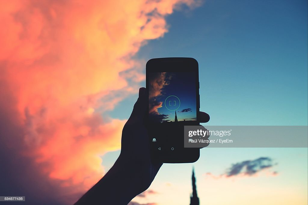 Cropped Image Of Silhouette Person Holding Cell Phone Against Sky At Dusk : ストックフォト