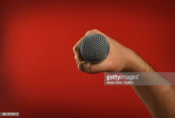 Cropped Image Of Singer Holding Microphone Against Red Background