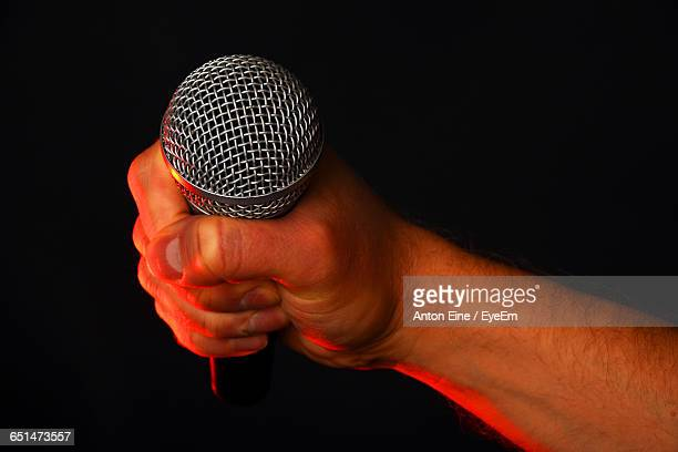 Cropped Image Of Singer Holding Microphone On Black Background