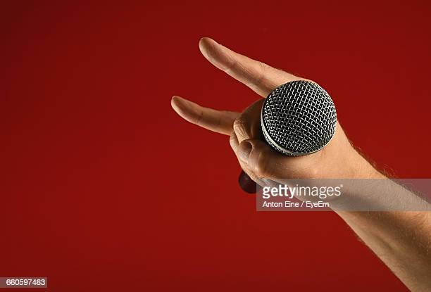 Cropped Image Of Singer Holding Microphone With Hand Sign Against Red Background