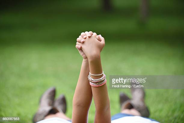 Cropped Image Of Sisters Holding Hands In Park