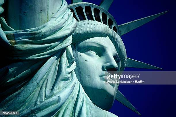 cropped image of statue of liberty against clear blue sky - statue of liberty stock pictures, royalty-free photos & images