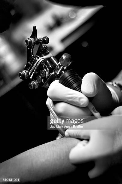 Cropped image of tattoo artist doing tattoo on arm