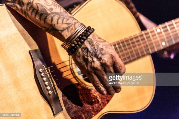 cropped image of tattooed hand playing guitar - andre wilms eyeem stock-fotos und bilder