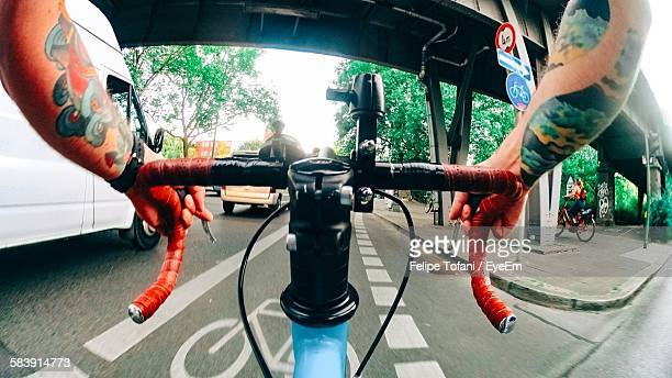 cropped image of tattooed man riding bicycle on road in city - kreuzberg stock photos and pictures