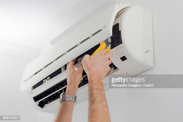Cropped Image Of Technician Servicing Air Conditioner