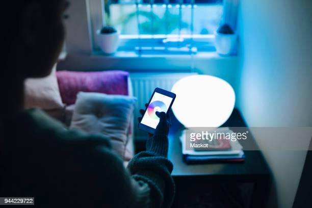 cropped image of teenage girl using smart phone while standing by illuminated bed in room - internet delle cose foto e immagini stock