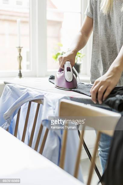 Cropped image of teenager ironing clothes at home