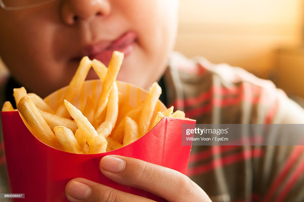 Cropped Image Of Tempted Boy Holding French Fries Packet : Foto de stock