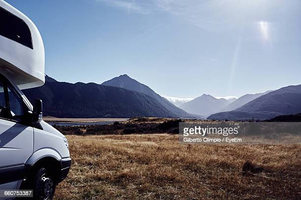 Cropped Image Of Travel Trailer On Grassy Field By Mountains Against Clear Sky