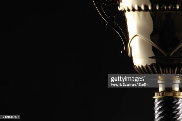 cropped image of trophy against black background - trofeo fotografías e imágenes de stock