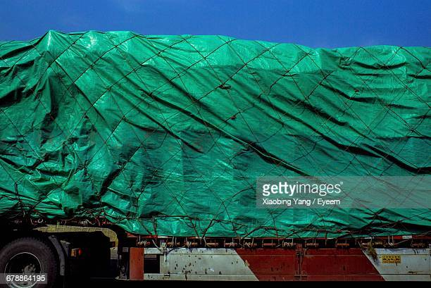 cropped image of truck covered with tarpaulin - tarpaulin stock pictures, royalty-free photos & images