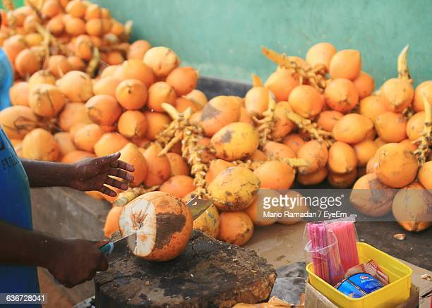 Cropped Image Of Vendor Chopping Coconut At Market Stall