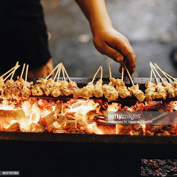 Cropped Image Of Vendor Cooking Satays