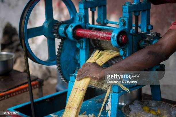 Cropped Image Of Vendor Holding Sugar Cane In Machinery