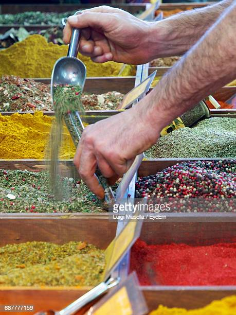 Cropped Image Of Vendor Pouring Spice In Container At Market