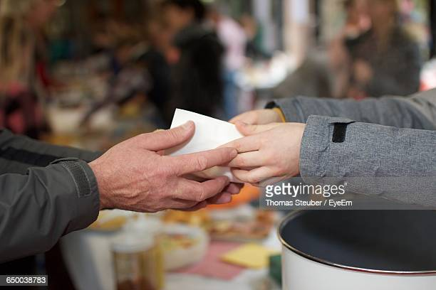 cropped image of volunteer giving food to person - charitable foundation stock pictures, royalty-free photos & images