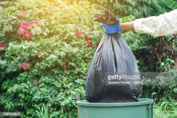 cropped image of volunteer holding garbage bag over can against trees - garbage can stock photos and pictures