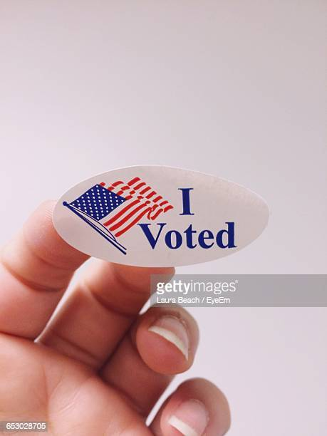 Cropped Image Of Voting Hand With American Flag Against White Background