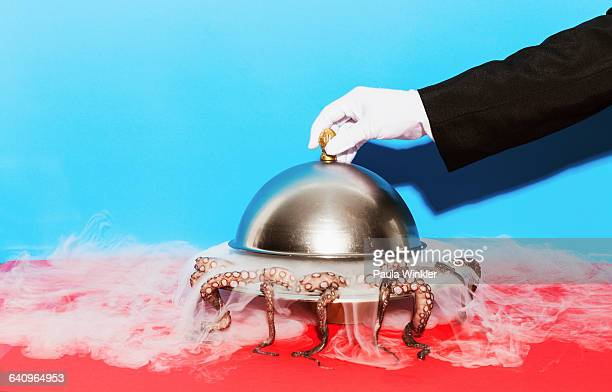 Cropped image of waiter lifting domed tray against blue background