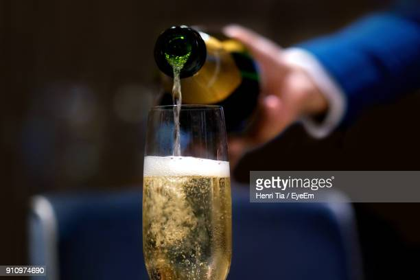 cropped image of waiter pouring champagne in flute - champagne stock pictures, royalty-free photos & images