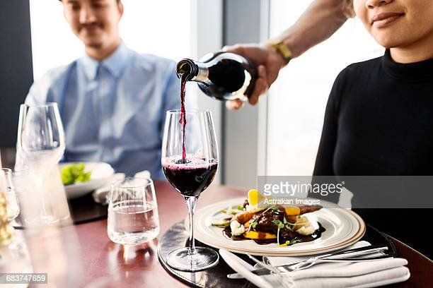 Cropped image of waiter serving red wine for female customer at restaurant