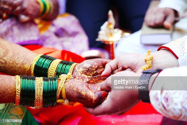 cropped image of wedding couple holding hands during ceremony - wedding stock pictures, royalty-free photos & images