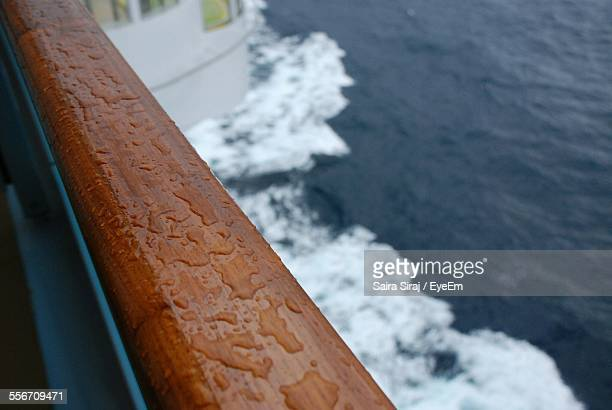 Cropped Image Of Wet Ship Railing On Sea
