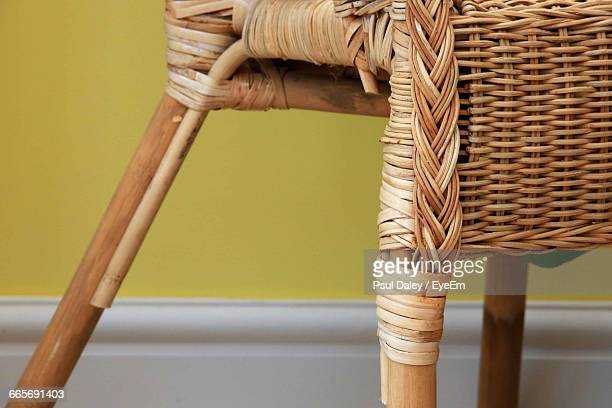cropped image of wicker chair against yellow wall - wicker stock pictures, royalty-free photos & images