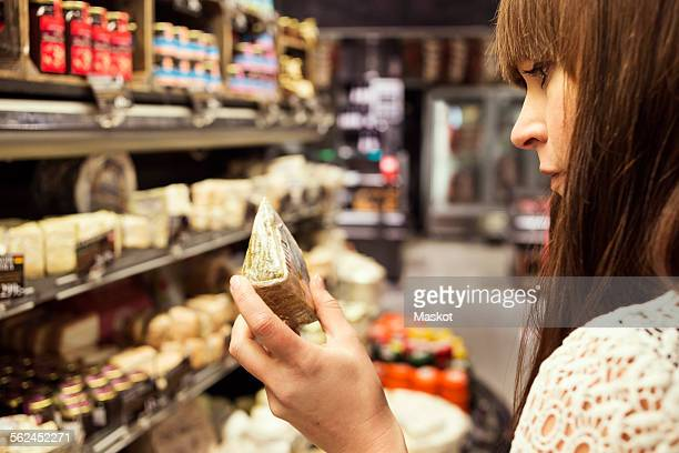 Cropped image of woman analyzing cheese in supermarket