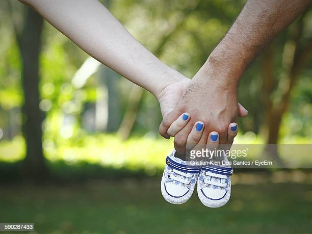 Cropped Image Of Woman And Man Hands Holding Baby Booties