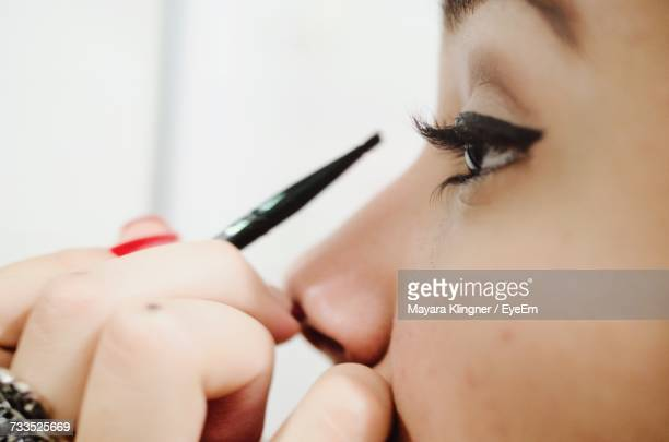 cropped image of woman applying eyeliner - eye make up stock photos and pictures