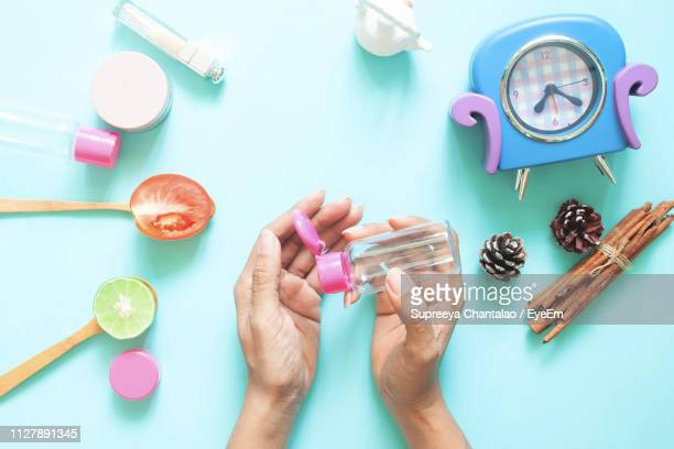 cropped image of woman applying hand sanitizer by personal accessories over colored background - hand sanitizer imagens e fotografias de stock