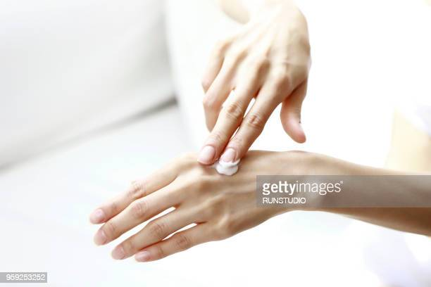 Cropped Image Of Woman Applying Lotion On Hand